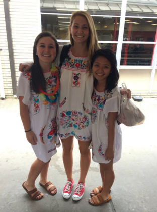 Friends Kelsey Cloud, Nancy Nguyen, and Maddie Tebbe, all seniors, smile for a group picture before a fiesta pep rally.