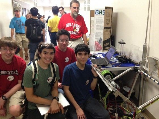 Robotics club members pose next to a machine they built that projects a ball up to 12 feet into the air. (From left) Matthew Dauber (sophomore), Henryk Viana (sophomore), Michael Murphey (junior), Andrew Advani (senior).