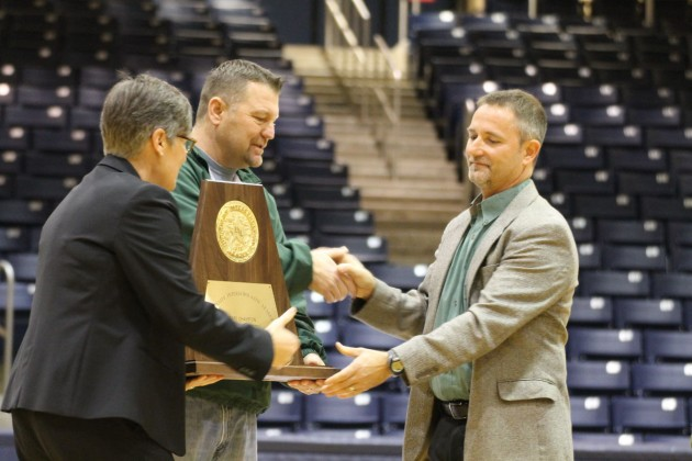 Head Cross Country Coach, Tony Brillon, accepts the state trophy from Athletic Director, Elliot Allen and Executive Director of Athletics, Paige Hershey. This is the second state trophy the cross country runners have been awarded. (Photo: Rebecca Williams