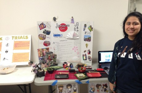 Aileen Martinez (junior) poses by her club poster decorated with Japanese elements and anime.