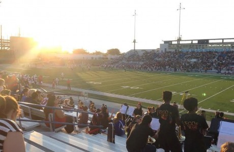 The sun sets behind the field as the game gets started.